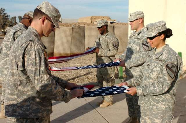 In the foreground, Greenfield, Ind. native Maj. Kurt Connell (left), operations officer for the 1st Brigade Special Troops Battalion; Capt. Sierra Symonette, assistant operations officer for the 1st BSTB, and other Soldiers fold flags at Camp Taji, Iraq Dec. 25 during a ceremony commemorating Continental Army Gen. George Washington crossing the Delaware River on Christmas Day 1776. (U.S. Army photo by Staff Sgt. Jon Cupp, 1st BCT, 1st Cav. Div. Public Affairs)