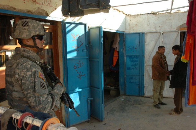Two Iraqis greet each other while Staff Sgt. Ryan Joseph, a Soldier on the personal security detail for MND-C commanding general Maj. Gen. Rick Lynch, stands by at the market in the village of Sadr al Yusifiyah. Lynch visited the village and PB Warrior's Keep Dec. 26.