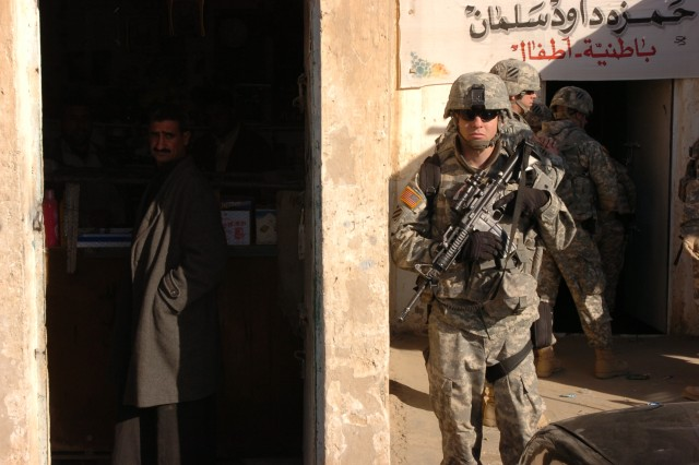 A Soldier from the personal security detail of the commanding general of MND-C, Maj. Gen. Rick Lynch, guards the entrance of a shop in Sadr al Yusifiyah during the CG's visit to the village and to PB Warrior's Keep Dec. 26.