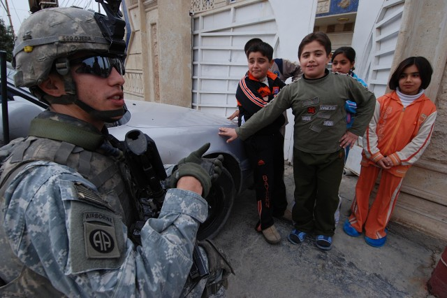 Staff Sgt. Eduardo Ojedo, a squad leader with A Co, Special Troops Battalion, 2nd BCT, 82nd Airborne Division, makes friends with local kids during a patrol of Baghdad's Suleik neighborhood.