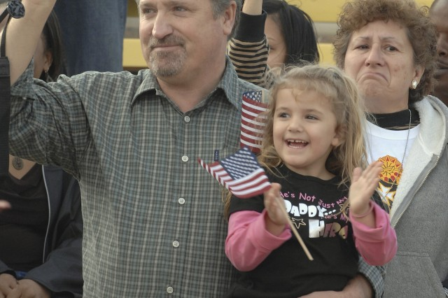 Paul Lacure and his granddaughter, Kiersty, await the arrival of her dad, Jerrett Lacure, during a welcome-home ceremony at Fort Hood, Texas.  Lacure is a member of the 1st Air Cavalry Brigade, returning from a 15-month deployment to Iraq.