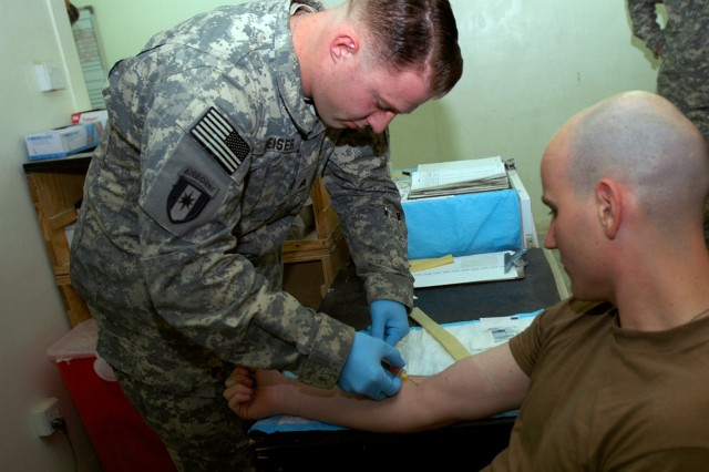 Sgt. Jonathan Weiser, a laboratory technician with U.S. Army Europe's Medical Troop, Regimental Support Squadron, 2nd Stryker Cavalry Regiment, practices drawing a blood sample from 2nd SCR colleague and combat medic Sgt. Brian Janek in the newly renovated Troop Medical Clinic at Camp Striker, Iraq. Improvements to the clinic include a pharmacy, X-ray area, lab, mental health facility and medical storage.