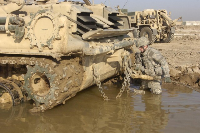 Spc. David Waiter, a welder on the vehicle recovery team of Company B, 610th Brigade Support Battalion, 4th Infantry Brigade Combat Team, 1st Infantry Division, hooks a cable to an entrenched M88 recovery vehicle during a training event at Forward Operating Base Falcon.