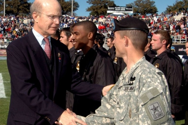 Secretary of the Army Pete Geren congratulates a group of Army Future Soldiers and their recruiters during halftime at the Armed Forces Bowl football game in Fort Worth, Texas, Dec. 31.