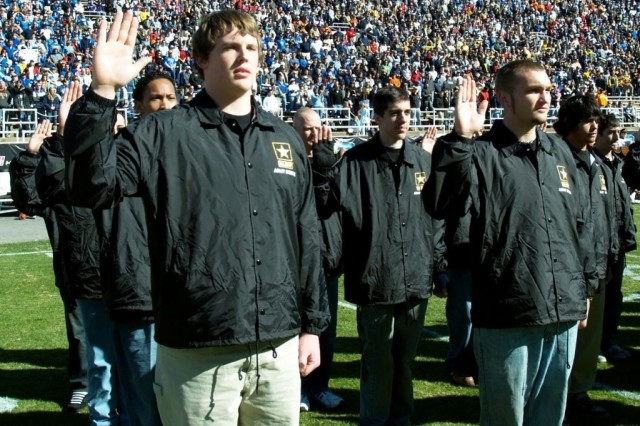 Army Future Soldier Trent Click (left) from Arlington Texas takes the oath of enlistment from Secretary of the Army Pete Geren during halftime at the Armed Forces Bowl football game in Fort Worth, Texas, Dec. 31.