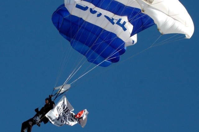 """An Air Force Cadet from the Air Force Academy's parachute team """"Wings of Blue"""" jumps the 'America Supports You' flag into Fort Worth, Texas' Amon G. Carter stadium prior to the start of the Armed Forces Bowl football game,"""