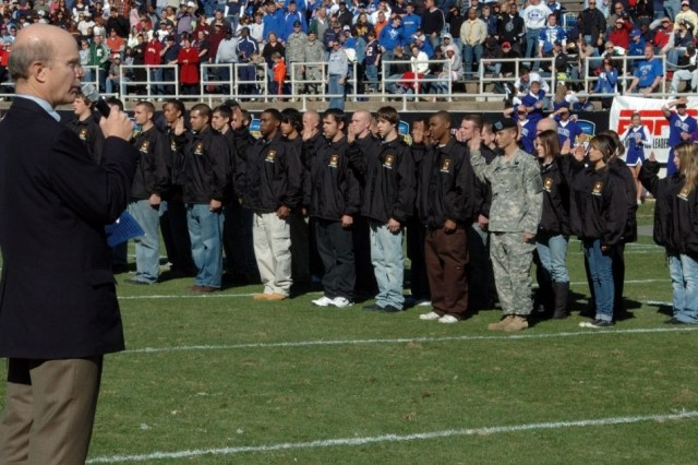Secretary of the Army Pete Geren swears-in 100 new recruits from all services during halftime at the Armed Forces Bowl football game in Fort Worth, Texas, Dec. 31.