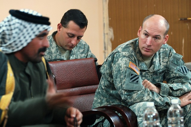 Col. James W. Adams, deputy commander of the 2nd Brigade Combat Team, 3rd Infantry Division, Fort Stewart, Ga., listens to a sheik's concerns during a meeting, Jan. 4, at Forward Operating Base Kalsu, while Staff Sgt. Shawn Wenninger, noncommissioned officer in charge of information operations, takes notes.