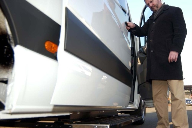 Tim Wood, U.S. Army Garrison Kaiserslautern logistics director, tests the automatic doorstep and movement alarm when a side door opens to one of the 14 vans going to Warrior Transition Units in Europe.