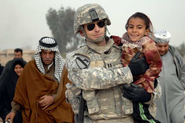 Capt. Keith Koppenhaver, 492nd Civil Affairs Battalion, carries a young Iraqi girl suffering from a chest tumor to the Taji Sports Complex for medical attention during a combined medical effort held in Iraq Jan. 1.