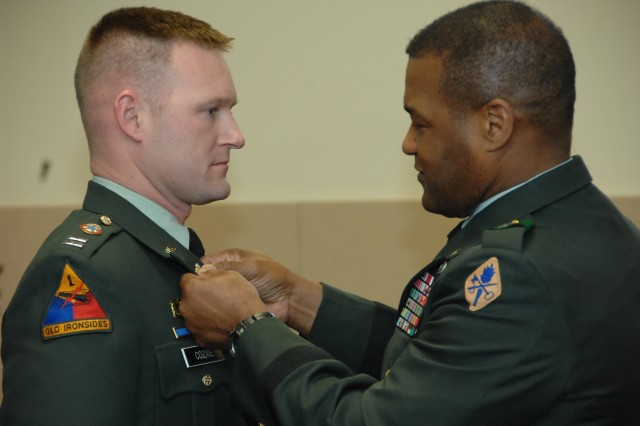 FORT LEE, Va. -  Brig. Gen. Jesse R. Cross, U.S. Army Quartermaster Center and School commanding general, pins the new Logistics Branch insignia on Capt. Brian Cozine, Combined Arms Support Command's  Concepts and Doctrine Directorate, during the Jan. 9 ceremony at Fort Lee