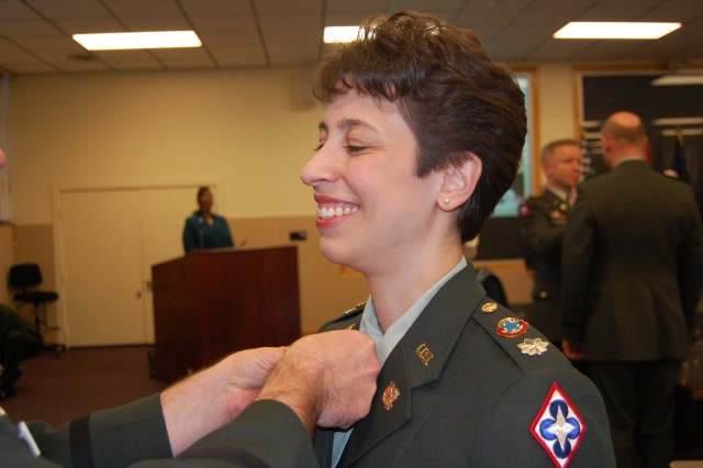 FORT LEE, Va. - Lt. Col. Vickie Stenfors, chief of the Logistics Branch Proponency Office, is all smiles as a fellow logistics officer pins the new insignia on her during the Logistics Branch exchange ceremony at Fort Lee Jan. 9.