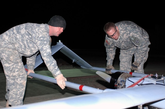 Army Spc. Mark Parrish (left), an unmanned aerial systems mechanic, and Army Staff Sgt. Terry Rust, maintenance noncommissioned officer in charge, both with the 4th Infantry Division's UAS Platoon, Company A, 3rd Special Troops Battalion, 3rd Brigade Combat Team, attached to Company G, Task Force 12, prepare an RQ7B Shadow 200 to be launched at the launch and recovery site at Camp Taji, Iraq, Jan. 6, 2008.