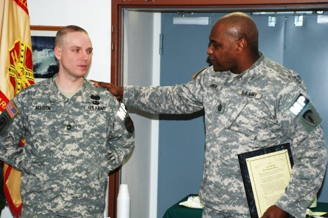 Sgt. Maj. Grant Jones, right, presents Sgt. 1st Class Christopher Allison a wall plaque of the NCO Creed during Allison's promotion ceremony.