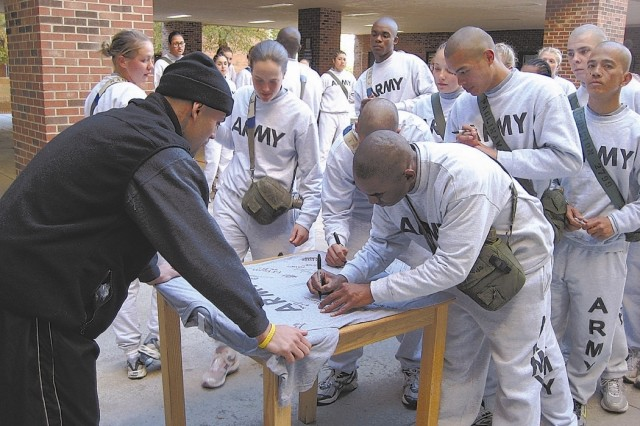 Basic Combat Training Soldiers from the 1st Battalion, 34th Infantry Regiment autograph an Army PT shirt for welterweight contender Luis Collazo. Collazo will wear the T-shirt to the ring for his next fight, scheduled for Jan. 19 on the undercard of Roy Jones Jr. versus Felix Trinidad.