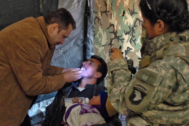 A dentist with the Iraqi Ministry of Health examines a man\'s teeth with assistance from Capt. Tran Quach-Miller, a dentist with Company C, 626th Brigade Support Battalion, 3rd Brigade Combat Team, 101st Airborne Division (Air Assault) during a coordinated medical engagement in the town of Abu Farris Jan. 12.