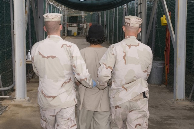JTF-Guantanamo guards escort a detainee to the detainee hospital located adjacent to Camp Four, Dec. 27. The U.S. government's program to transfer and release detainees is unprecedented during a time of war, officials said. (