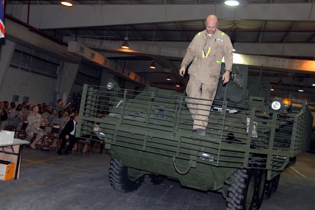 Gary Roberts, General Dynamics Land Systems\' contractor, steps off the 100th repaired Stryker at Camp As Sayliyah during a recognition ceremony in Qatar Jan. 12.
