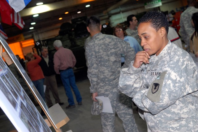 U.S. Army Sgt. 1st Class Catherine Dorsey, from Montgomery, Ala., reviews the history of the 100th repaired Stryker at Camp As Sayliyah after a recognition ceremony in Qatar Jan. 12.