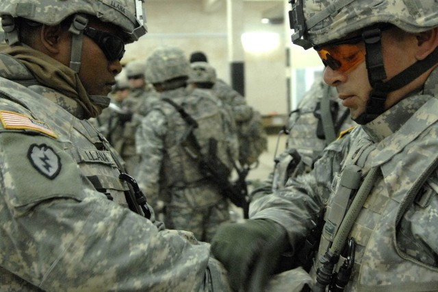 Soldiers conduct buddy checks at Camp Taji, Iraq, before starting a resupply mission to combat outposts and joint security stations. The Soldiers are from the 1st Cavalry Division and the 25th Infantry Division.