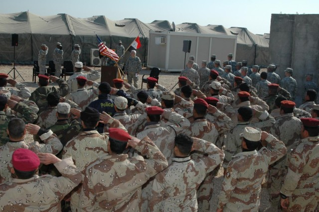 Attendees at a welcoming ceremony for the first-ever class of trainees to attend the new Task Force Marne Noncommissioned Officer Academy salute the flag during the Iraqi national anthem at Forward Operating Base Kalsu, Iraq, Jan. 15.