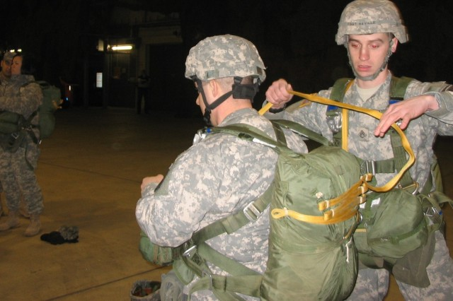 Staff Sgt. David Beville (right) inspects the parachute of Spc. Andrew Finkler before a jump over Germany. The 67th Forward Surgical Team recently attained airborne status and was accordingly allowed to don the maroon beret. Beville is assigned to the 5th Quartermaster Company and Finkler is assigned to the 67th FST (Airborne).