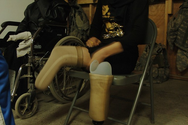 An Iraqi woman with prosthetic legs prepares to go to a physical therapy session on Patrol Base Assassin, Iraq, Jan. 10, where Soldiers from the 3rd Infantry Division are stationed. The woman lost both legs three years ago during an enemy rocket attack in Rustamiyah.