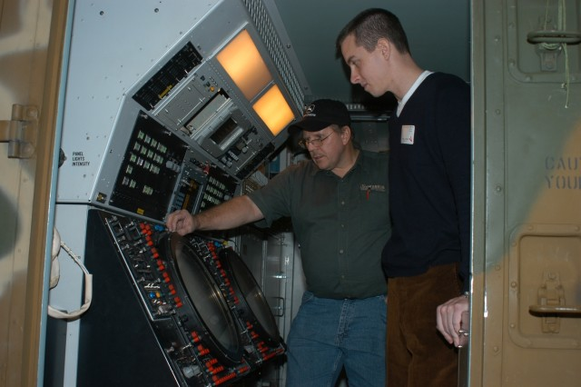Paul Manarchuck, electronic integrated systems mechanic, explains the functions of an AN/TPS-75 Air Defense Surveillance Radar hot mock up to Capt. Dan Johnson, who toured depot facilities on Dec. 27. The hot mock up is used at the AN/TPS-75 Air Defense Surveillance Radar Test Facility.  Johnson, an air battle manager, used the TPS-75 radar while on duty in Southwest Asia.
