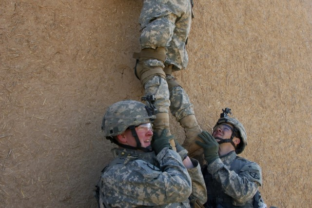 Pfc. Ryan Mahan and Spc. Stephen McLain hoist Pfc. Ryan Springstead as he looks over a wall to see if they can enter a house through the roof of a building in Chinchal, Iraq.  The Soldiers are assigned to 3rd Platoon, Troop A, 1st Squadron, 71st Cavalry Regiment, 1st Brigade Combat Team, 10th Mountain Division and the operation took place earlier this month.