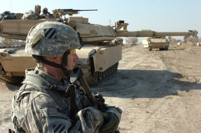 Sgt. Stuart Arnold, personal security detail, Headquarters and Headquarters Company, 2nd BCT, 3rd Infantry Division, pulls security in front of Combat Outpost Meade with an Abrams tank in the middle ground and a Bradley vehicle in the background Jan. 16.