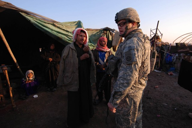 1st Lt. Austin Dziengelewski, a platoon leader with Company B, 2nd Battalion, 325th Airborne Infantry Regiment, 2nd BCT, 82nd Airborne Division, gets information from a family of displaced squatters after discovering their refugee camp during a patrol Jan. 14. Later that night, the paratroopers dropped off some supplies to help the family get through the winter.
