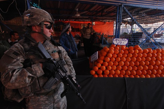 Sgt. 1st Class Jorge Mazuela, a platoon sergeant with Company B, 2nd Battalion, 325th Airborne Infantry Regiment, 2nd BCT, 82nd Airborne Division, keeps a watchful eye out for security risks while shoppers during a visit to one of the thriving new market areas in Baghdad's Sha'ab neighborhood Jan 15.