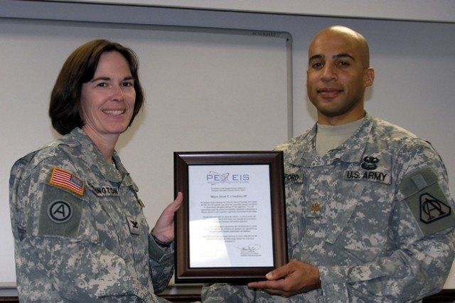 Col. Gale Harrington (left), the Project Manager, Defense Communications and Army Transmission Systems, makes remarks before presenting the charter to Maj. Jake Crawford III (right) for his new assignment as Assistant Project Manager, Vehicular Intercom Systems in a ceremony at Ft. Monmouth, N.J. on Nov. 16.