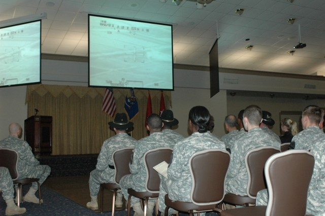 Soldiers with the 1st Cavalry Division watch the gun footage from the battle in An Najaf, Iraq, that resulted in Chief Warrant Officer 3 Zachary Johnson, a pilot with 4th Battalion, 227th Aviation Regiment, being awarded the Distinguished Flying Cross at the Fort Hood Catering and Conference Center Jan. 28. Johnson, a Nampa, Idaho, native, who was the pilot-in-charge and air mission commander,  was commended for his calm demeanor and reasoning skills during the heat of battle.