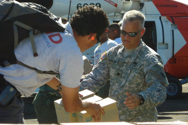 Ricardo Herrera, OFDA, hands relief supplies to U.S. Army South's HAST leader, Lt. Col. Kevin J. Charlton, during a November disaster-response mission in the Dominican Republic. Charlton and the HAST are on in Bolivia to assess damage there from recent floods.