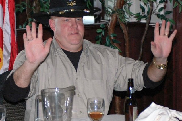 Lt. Col. Russell Cavin, 15th Sustainment Brigade's deputy commander, throws his hands up in a gesture to stop the laughing as someone in the crowd jokes about him.  Cavin was bid farewell at the dinner along with 16 other non-commissioned and commissioned officers from both the 15th Sus. Bde., and 15th Special Troops Battalion.