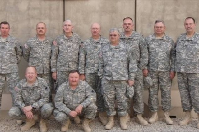 Members of the Joint Munitions Command ammunition assessment team take a break to pose for a team picture while in Southwest Asia. The assessment took place during 100-day deployment. Back Row:  Jim Gahagan, Mike Griffith, Bob Wild, Ed Averill, John Barton, Bill Sykes, Jim Gray Front Row:  Doug Maddox (kneeling), Dave Tipp (kneeling), Jim Young (standing).