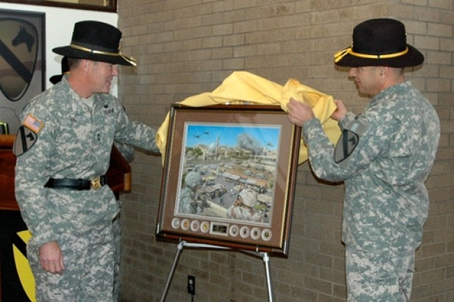 """Maj. Gen. (P) Joseph F. Fil, Jr., 1st Cavalry Division's former commanding general (left), and his top noncommissioned officer, Command Sgt. Maj. Philip Johndrow, lift a cloth off of a print by Jody Harmon titled """"The Surge"""" during an unveiling ceremony Feb. 1 at the division's headquarters on Fort Hood, Texas, prior to a relinquishment of command ceremony."""