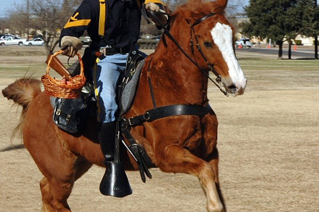 "Sgt. Justin Lidgett, 1st Cavalry Division, Horse Cavalry Detachment rider, speeds off on his horse Homer after receiving a gift of carrots for the horse from Kassi Piggee at the 15th Special Troops Battalion Change of Command Ceremony at Fort Hood, Texas Jan. 31. Lidgett has rode with the Horse Detachment for five years and said, ""It's one of the best jobs in the Army."""