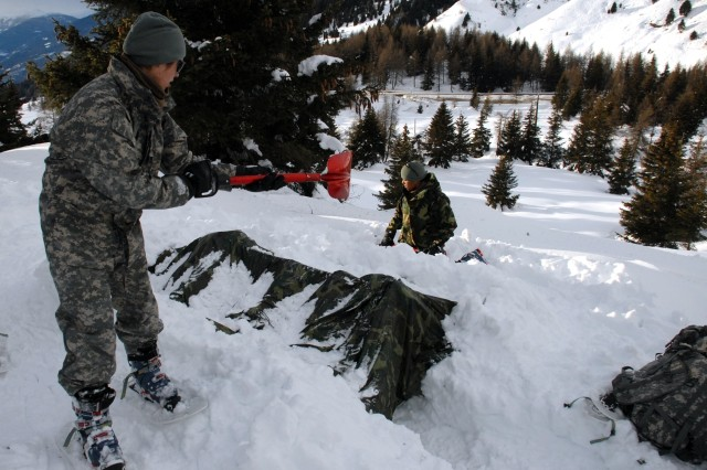 Sgt. Margarita Gutierrez of U.S. Army Europe's 13th Military Police Company shovels snow on a shelter to provide some natural insulation from the cold, during a four-week U.S.-Italian winter survival training course in the Dolomite Mountains of northern Italy.