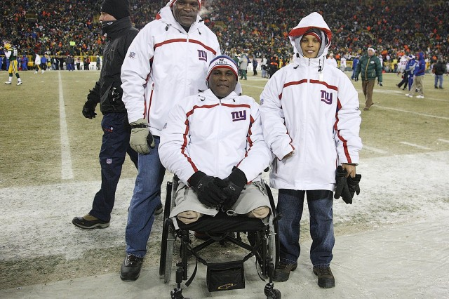 Lt. Col. Greg Gadson (center), an honorary team captain for the N.Y. Giants, is shown here with his son Jaelen and Hall of Fame Linebacker Harry Carson during the National Football Conference Championship game Jan. 20 at Lambeau Field in Green Bay, Wisc.