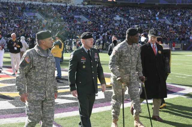 Lt. Col. Greg Gadson (second from right) walks off the field on his two prosthetic legs Dec. 5 after the coin toss for the Army-Navy game.  He is accompanied by Army Chief of Staff Gen. George Casey Jr., Superintendent of West Point Lt. Gen. Buster Hagenbeck, and Secretary of the Army Pete Geren.