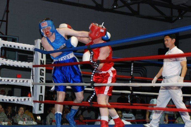 Garrett Stokes, HHC, 1st Bn., 72nd Armor Regt., 1st HBCT, pins his opponent, Joseph Smith, Co. E., 2nd Bn., 9th Inf. Regt., 1st HBCT, against the ropes during the Warrior Country Boxing Invitational Jan. 19 at Camp Casey's Hanson Field House.