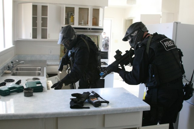Two members of Fort Rucker's Special Reaction Team search a Bowden Terrace housing area home during an evaluated exercise Jan. 25.