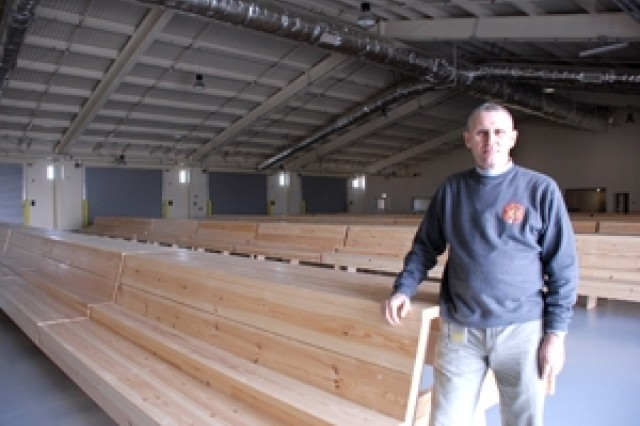 Martin Fano, director of the Arrival/Departure Airfield Control Group, U.S. Army Garrison Vicenza, shows off the custom-built Swedish pine seats designed for paratroopers in the new Personnel Alert Holding Area at Aviano Air Base, Italy