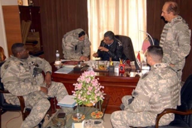 An interpreter helps Capt. Vaughan Byrum of the 18th Military Police Brigade's Police Transition Team (left) and brigade operations officer Lt. Col. Thomas Lombardo (right) discuss enhanced Police Transition Team methods with Brig. Gen. Safaa, deputy commander of the Iraqi Police Patrol Headquarters, in Baghdad, Iraq Feb. 6