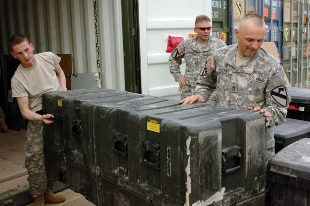Sgt. Matthew Stark and Sgt. 1st Class David Botts, both of Headquarters and Headquarters Troop, 3rd Brigade Combat Team, 1st Cavalry Division, unload a heavy container while unloading their unit's shipping containers.  Cleaning out containers is one step towards reintegrating into garrison life after being deployed for 14 months in Iraq.