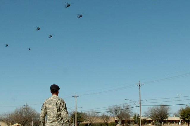 Lt. Col. Christopher Joslin, the commander of the 2nd Battalion, 227th Aviation Regiment, 1st Air Cavalry Brigade, 1st Cavalry Division, watches from the First Team's patch on Cooper Field as eight of his battalion's UH-60 Black Hawk helicopters fly over the division's parade field on their return flight to Fort Hood Feb. 8. These helicopters were unloaded from cargo ships near Beaumont, Texas, and reassembled before they were able to return to Fort Hood, Texas.