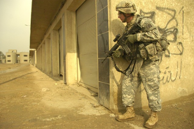 1st Sgt. Kenneth Kempke, with Company D, 2nd Combined Arms Battalion, 69th Armor Regiment, 3rd Infantry Division, secures a market development project area in New Baghdad, Iraq.