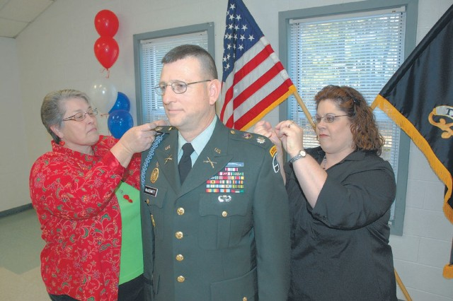 Newly promoted Lt. Col. Richard MacDermott, executive officer, Task Force Marshall, has his new rank insignia pinned on by his wife Patricia (left) and his daughter Jennifer Moss during a promotion ceremony Friday at McCrady Training Area. MacDermott has gone from a second lieutenant to major, from major to sergeant, from sergeant to sergeant first class, from sergeant first back to major to his new rank